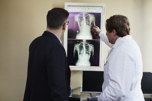 Doctor and Patient Examining X-Ray of Adult Scoliosis
