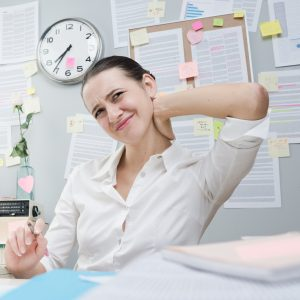 Woman in Office Experiencing Work-Related Back Pain