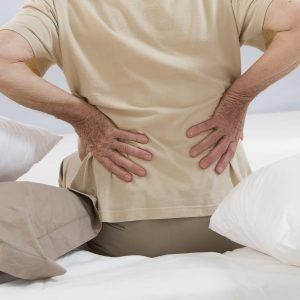 Person Sitting on Bed Experiencing Lower Back Pain