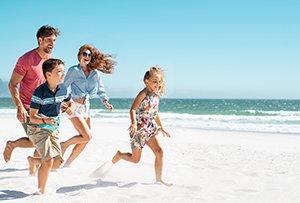 Happy family running on the beach.